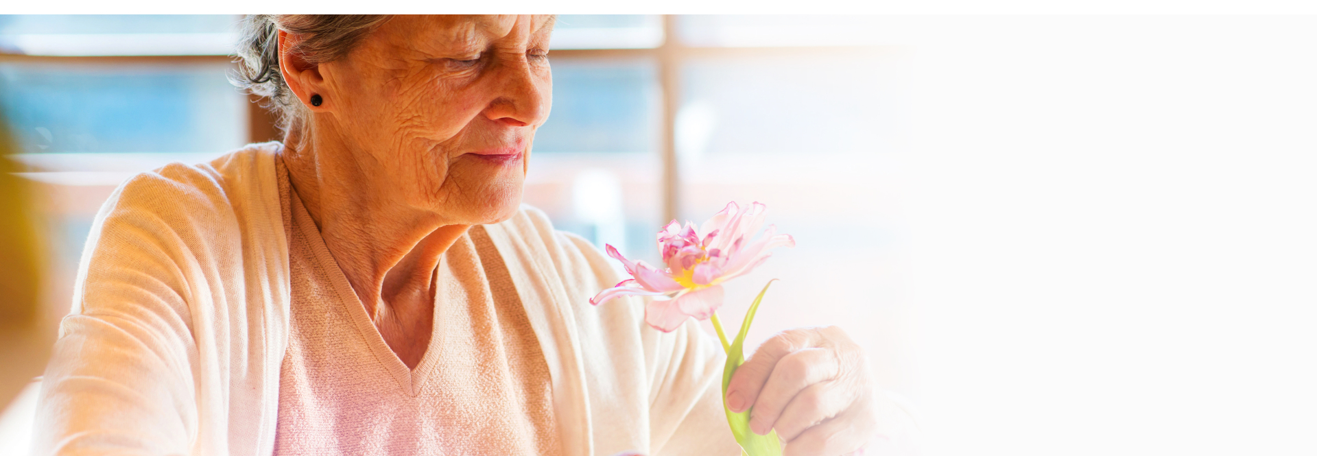 old woman holding a flower